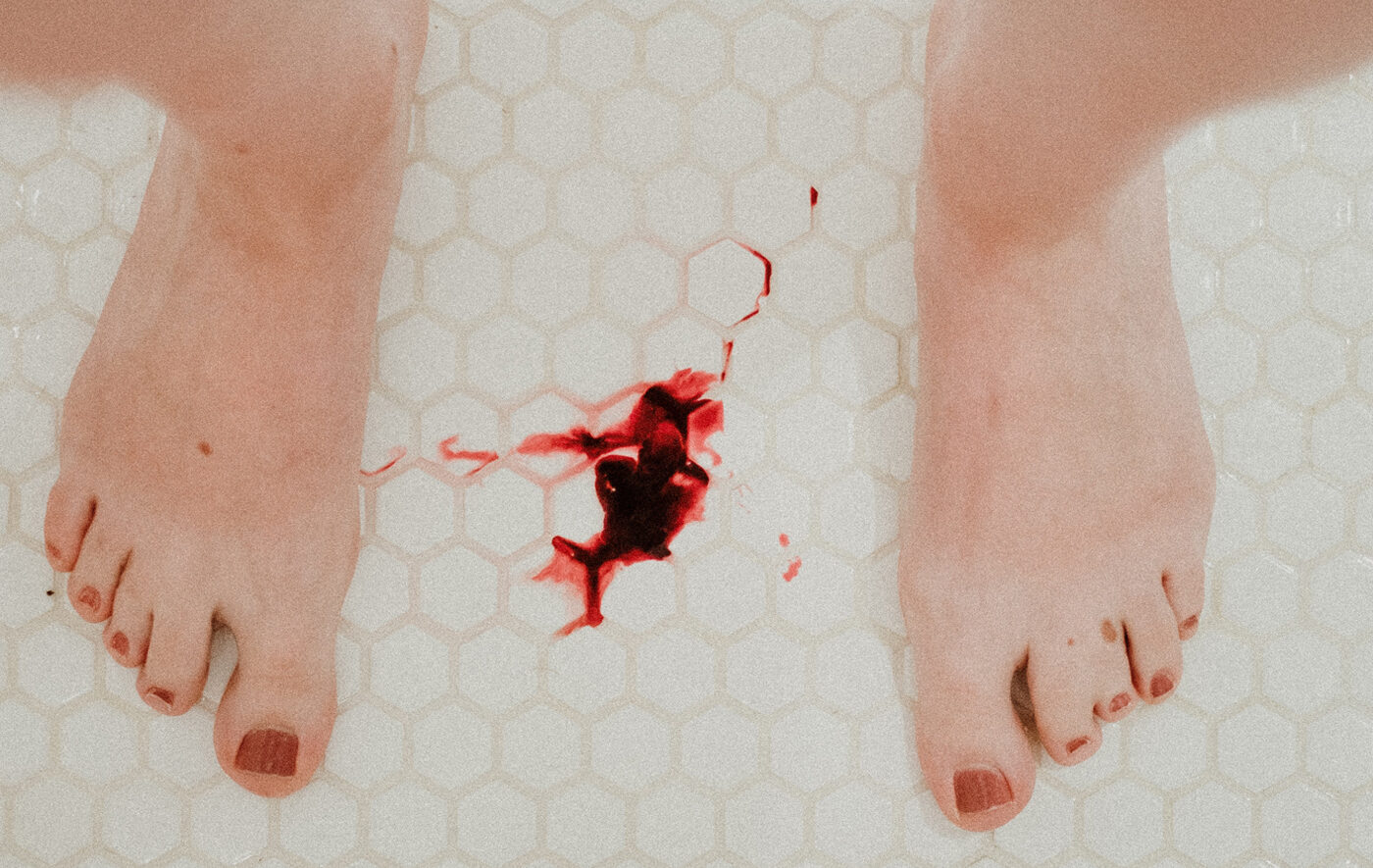 A woman standing in a white shower with period blood on the floor between her feet