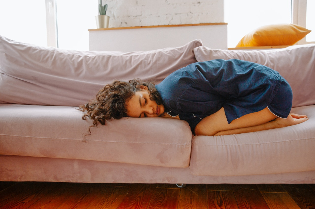 A woman with brown hair lying curled up on the sofa in her pyjamas in pain